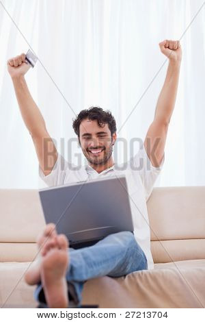 Portrait of a cheerful man shopping online in his living room