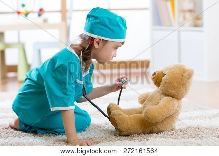 Funny child girl playing with teddy bear and pretending she is a doctor in hospital poster
