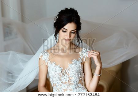 Beautiful Young Bride With Wedding Makeup And Hairstyle In Bedroom. Beautiful Bride Portrait With Ve
