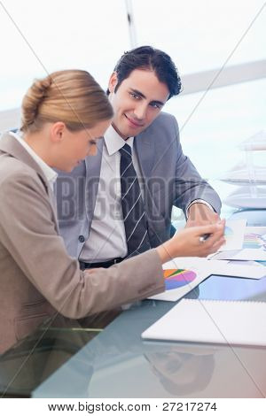 Portrait of business people looking at statistics in a meeting room