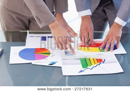 Hands of business people studying statistics in a meeting room