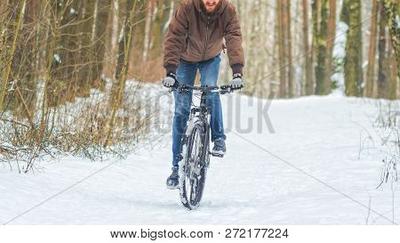 Cyclist Riding The Mountain Bike In Winter Forest. Uphill Riding On Mtb