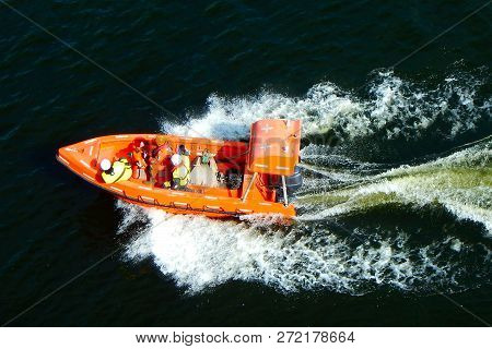 People In Lifeguard Jackets In Orange Rescue Safe Boat With Sea Around