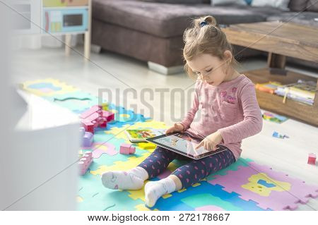 Cute Little Girl Is Using A Digital Tablet  Sitting On The Floor At Home  In The Middle Of Toys.