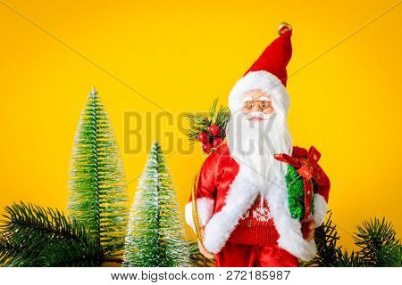 A Santa Claus figure with fir trees on yellow background