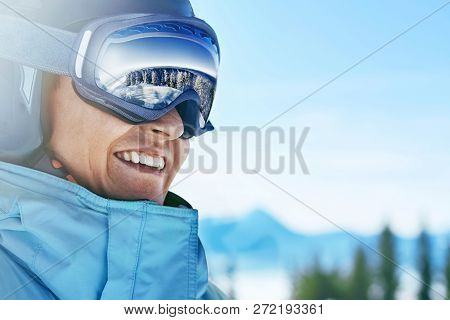 Close Up Of The Ski Goggles Of A Man With The Reflection Of Snowed Mountains.  A Mountain Range Refl