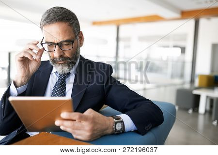 Shot Of Thinking Financial Advisor Businessman Working In Office.