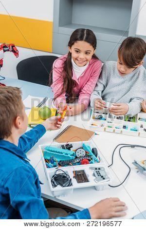 preteen schoolchildren making robot with details in stem education class poster