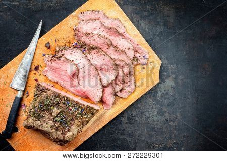 Traditional lunch meat with sliced cold cuts roast beef as top view on a cutting board with copy space right
