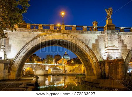 Night View Of Ponte Sant Angelo, Holy Angel Bridge, And Tiber In Rome, Italy