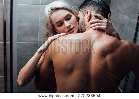 Affectionate Heterosexual Couple Hugging And Kissing While Taking Shower Together