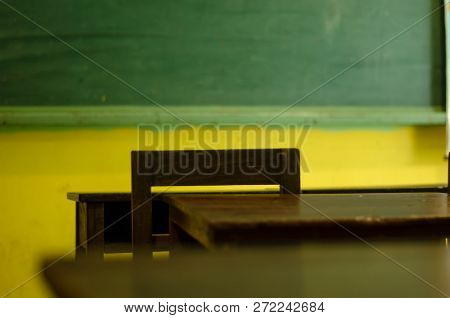 Asian Vintage Classroom,compose By Green Board ,wood Table And Chair From The Back Of Room Corner