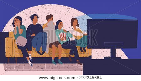 Group Of Friends Sitting On Sofa Or Couch In Darkness And Watching Scary Movie. Young Girls And Boys