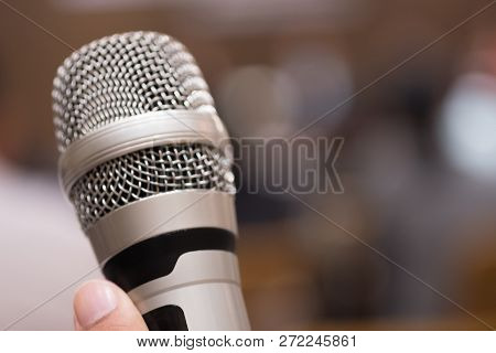 Hands Holding Microphones For Speaking In Seminar Room Convention Hall Background. Seminar Conferenc