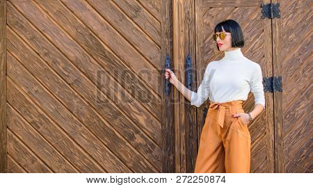Woman Walk In Loose Pants. Woman Fashionable Brunette Stand Outdoors Wooden Background. Girl With Ma