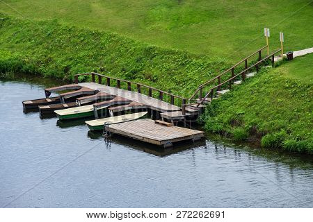 Boat Station On The River And A Green Meadow, Summer Day, Boats On The Shore Of The River