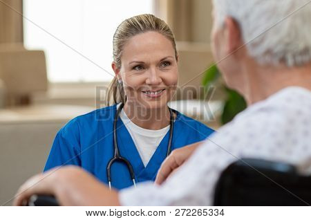 Smiling beautiful nurse in front of patient on wheelchair at hospital. Young friendly doctor consoling disabled senior man. Supportive young nurse looking at senior man sitting in wheelchair.