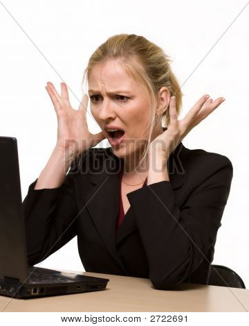 Attractive blond hair woman wearing business suit sitting in front of a computer with angry facial expression with hands up while looking at the computer as if it crashed or broke poster