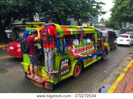Cebu, Philippines - October 01, 2018: Colorful Typical Bus Jeepney Overloaded With Passengers Hangin