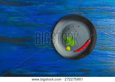Black Ceramic Plate On A Dark Blue Wood Surface With Addition Of Fresh Herbs, Chili Pepper And Spice