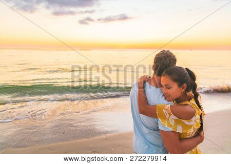 Couple in love embracing each other lovers relaxing on beach watching sunset - Asian girlfriend affectionate - love and tenderness on travel summer holidays.