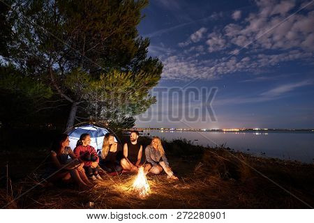 Group Of Five Travellers, Young Man And Women Sitting On Sea Shore At Campfire Under Tree. Tourist T