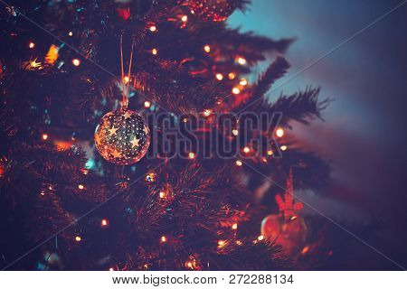 Beautiful Christmas tree in dark evening light with festive xmas lights on it, cozy family holiday at home, happy winter holidays