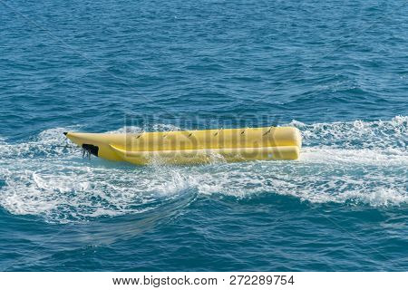 Empty Inflatable Yellow Banana Boat In The Sea. Banana Boat For Fun On Water Surface In Summer Day -