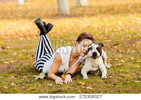 Girl In Black And White Clothes With Black And White Dog Stafford Play On The Ground At Park Outdoor