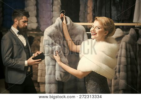 Woman In White Fur Coat With Bearded Macho Looking For New Overcoat. Girl With Cunning Face Wearing