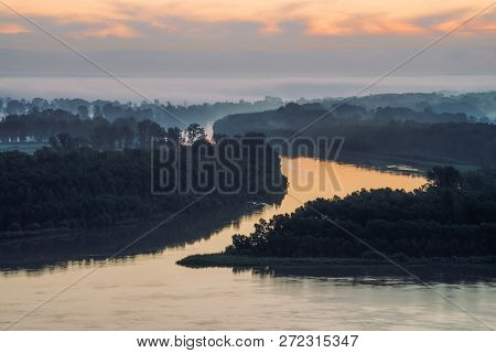 Early blue sky reflected in river water. Riverbank with forest under predawn sky. Cloudy sunrise sky on background. Fog hid trees on island. Colorful morning atmospheric landscape of majestic nature. poster
