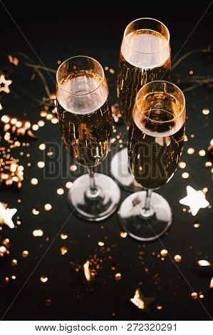 Three Glasses Of Champagne On Holiday Black Background With Golden Decoration. Top View. Festive Con
