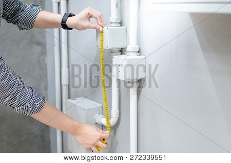 Male Hand Electrician Using Tape Measure For Measuring Dimension Of Electrical Conduit And Electrica