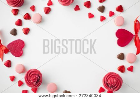 valentines day, sweets and romantic concept - close up of frosted cupcakes, red heart shaped chocolate candies, macarons and lollypops on white background