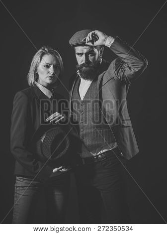 Man And Woman In Retro Suit And Hat On Dark Background. Couple In Love With Suspicious Face Working