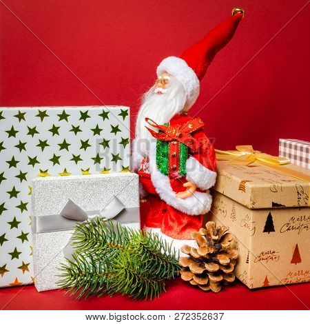 An image of a Santa Claus figure standing on a golden gift box