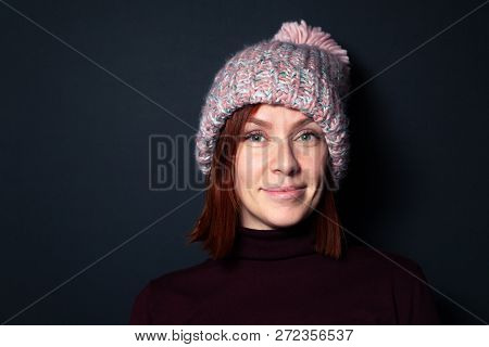 Beautiful Young Redhead Girl In A Purple Sweater And Pink Knitted Hat With Pompon Dressed Sideways S