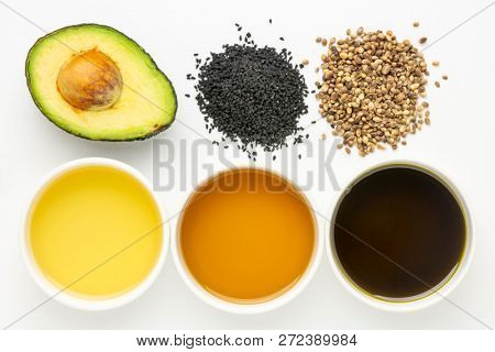 health oils from avocado, black seed and hemp seeds - top view of ceramic bowls with corresponding seeds and fruit
