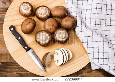 Fresh And Sliced Chestnut Mushroom With Small Knife On A Wooden Board