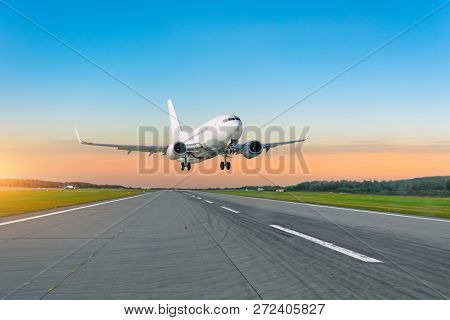 Passenger Plane Fly Up Over Take Off Runway From Airport At Sunset.