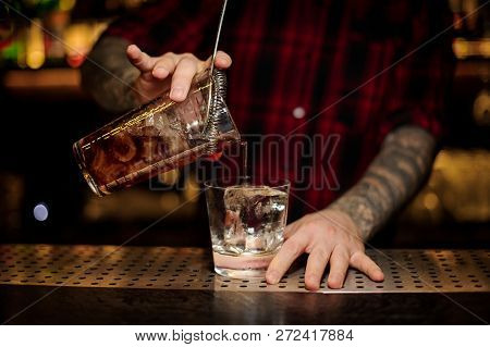 Bartender Pouring A Godfather Cocktail From The Measuring Cup