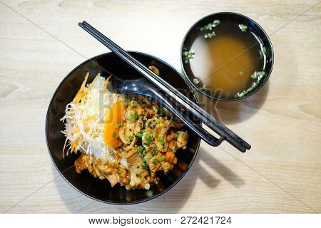 Rice With Grilled Pork Teriyaki And Spring Onion On Top In The Black Plastic Bowl With Soup For Japa