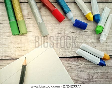 Art Supplies Including Pencil, Water Colour, Glitter And Blank Paper On Wooden Background