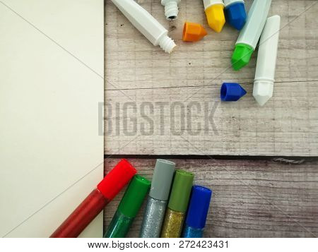 Art Supplies Including Water Colour, Glitter And Blank Paper On Wooden Background. Copyspace
