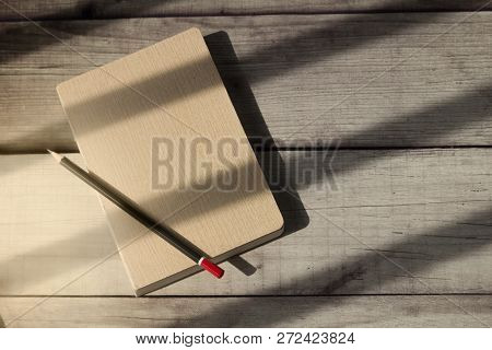 Blank Book And Pencil On Wooden Table With Sunlight Shone Over It.