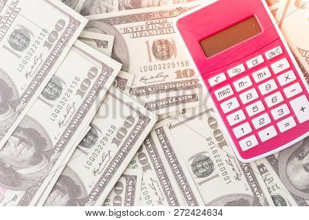 Concept Of Tax And Finance With Calculator On Piles Of Money