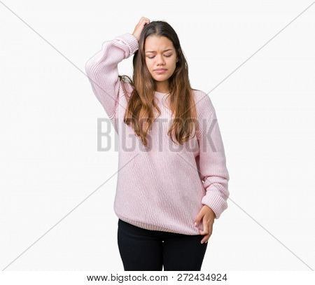 Young beautiful brunette woman wearing pink winter sweater over isolated background confuse and wonder about question. Uncertain with doubt, thinking with hand on head. Pensive concept.