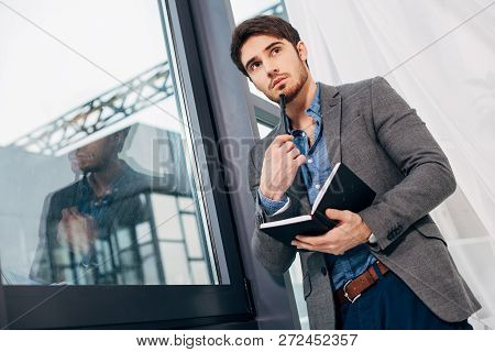 Thoughtful Businessman Standing By Window With Open Notebook And Pen In Office