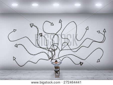 Businessman Trying To Choose The Right Path. Chaotic Arrows Leading To Different Directions.