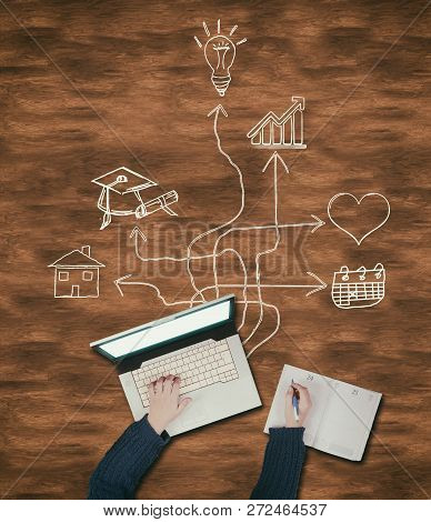 Top View Of Hands Writing On Laptop And Notebook On A Wooden Table, Drawn With Arrows Leading To Dif